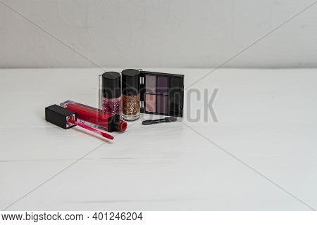 Liquid Lipstick With Applicator, Eyeshadow Palette And Colorful Nail Polish Isolated On White With C