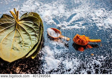 Ayurvedic Remedy For Sour Throat Consisting Of Betel Leaves, Turmeric, And Salt On A Black Wooden Su