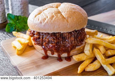 Hot, Fresh Pulled Pork Barbecue Sandwich With French Fried Potatoes On A Cutting Board