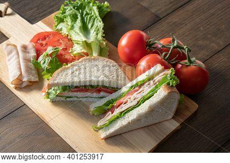 Fresh Turkey, Lettuce And Tomato Sandwich Cut In Half On Cutting Board