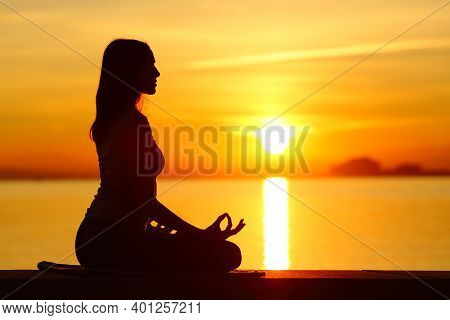 Side View Portrait Of A Silhouette Of A Woman Doing Yoga Exercise At Sunset On The Beach