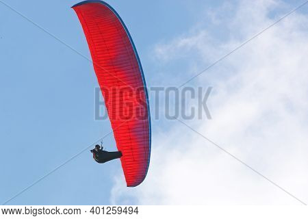Paraglider Flying Red Wing In A Blue Sky