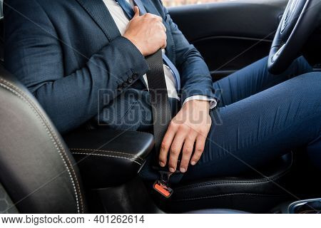Cropped View Of Businessman Locking Seatbelt In Car On Blurred Foreground.