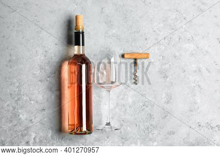 A Bottle Of Rose Wine, A Glass Of Wine And A Corkscrew On A Gray Concrete Grunge Background. Top Vie