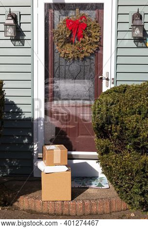 Packages Delivered To Front Door Of A Residential House With A Wreath Hanging Close To The Christmas