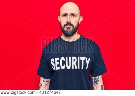 Young handsome man wearing security t shirt thinking attitude and sober expression looking self confident