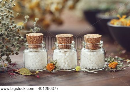 Bottles Of Homeopathic Globules And Medicinal Herbs. Homeopathy Medicine Concept.