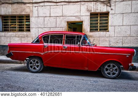 Havana, Cuba, July 2019, View Of A Red 1950's American Classic Car Parked In An Old Part Of The Capi