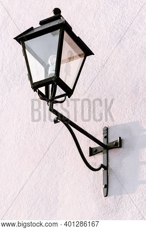 Black Vintage Streetlight On A Pale Pink Wall In A European Town.