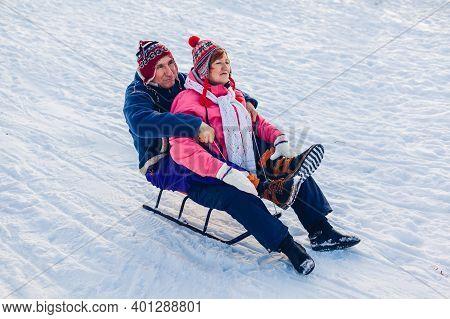 Sleigh. Senior Couple Sledding Downhill. Family Having Fun Sitting On Sleigh In Winter Park. Winter