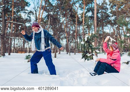 Senior Couple Sledding. Man Carrying His Wife On Sleigh. Happy Family Having Fun In Winter Park. Out