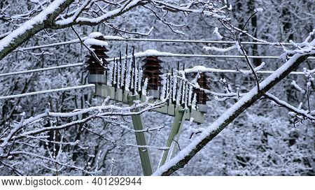 Frozen Insulators On A High Voltage Pole In The Forest