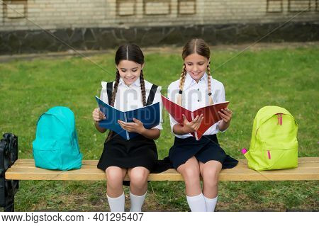Little Kids In School Uniforms Read Library Books Sitting On Bench Outdoors, Reading.