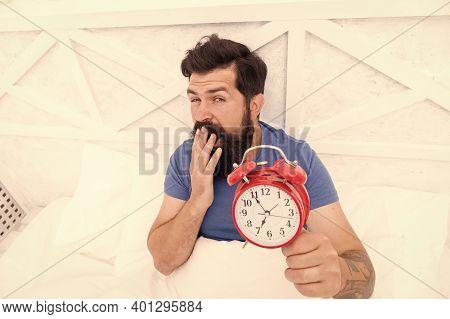 Bearded Guy Yawning With Alarm Clock. Bearded Man Clock Ticking. Sleep Longer. Man Hipster Want To S