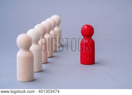 Leadership Concept, Red Figure Of A Man Made Of Wood, Standing Out From The Crowd Of. Different Peop
