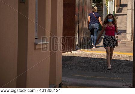 Brazilian Woman Dressed In Red Wearing Mask Walking On The Sidewalk