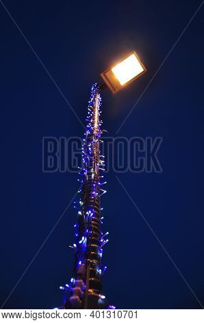 Blur Image Of Metal Lamppost Decorated With Bright Blue Light At Night