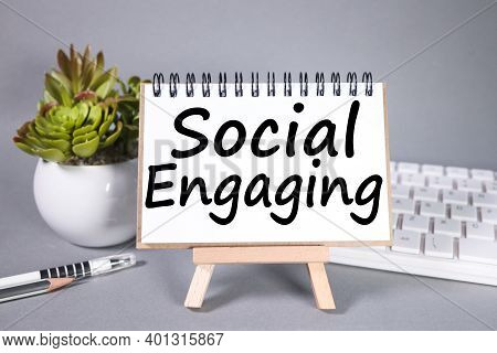 Social Engaging, Text On White Paper On Gray Background. Near The Keyboard And Plants