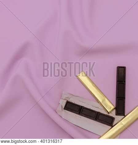 Portion Pieces Of Chocolate In The Form Of Sticks. Some Are Wrapped In Golden Paper, Others Are Unro