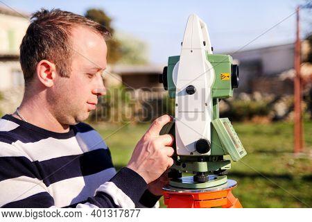 Man Using Of Total Station. Guy Surveyor At Work. Survey Instrument Geodetic Device, Total Station S