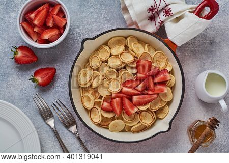 Mini White Pancake Cereal With Strawberries In Frying Pan For Breakfast On Grey Background . Trendy