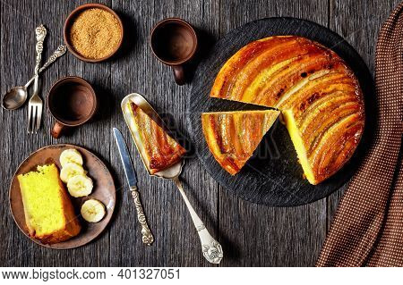 Upside-down Banana Cake On A Black Round Stone Plate On A Rustic Wooden Table, Horizontal View From