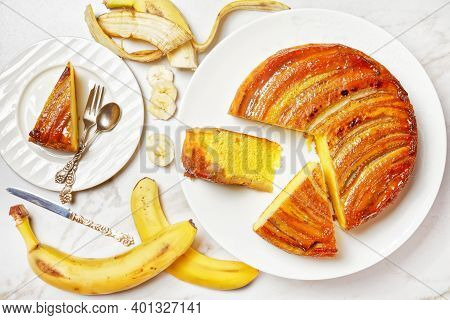 Upside Down Banana Cake On A White Plate On A Marble Table, Horizontal View From Above, Flat Lay