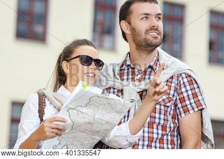 Vacations And Traveling Ideas. Positive Caucasian Couple Traveling Around City With Camera. Looking