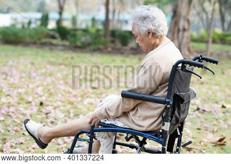 Asian Senior Or Elderly Old Lady Woman Patient Pain Her Knee On Wheelchair In Park, Healthy Strong M