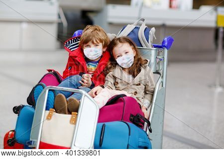 Two Little Kids, Boy And Girl Wearing Medical Masks At The Airport. Happy Children, Family Travel To