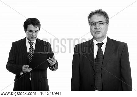 Senior Persian Businessman Wearing Eyeglasses And Young Persian Businessman Reading On Clipboard