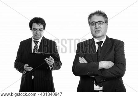 Senior Persian Businessman With Arms Crossed And Young Persian Businessman Reading On Clipboard