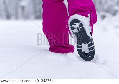 Women Hiking In Winter Forest By Snow In Hiking Shoes Boots. Winter Hiking.
