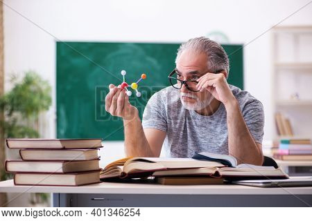 Old male physicist student in the classroom