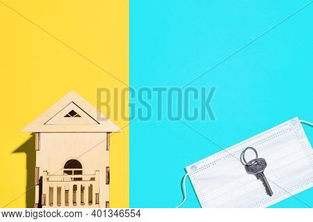 Toy House And Metal Key Lying On Medical Mask, Top View. Multicolored Background, Copy Space. Concep