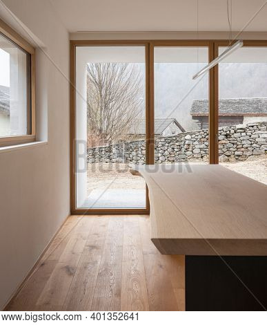 Modern house interior with white walls and parquet floors. Detail of wooden table with design lamp and window to the forest of the Swiss Alps.  Nobody inside