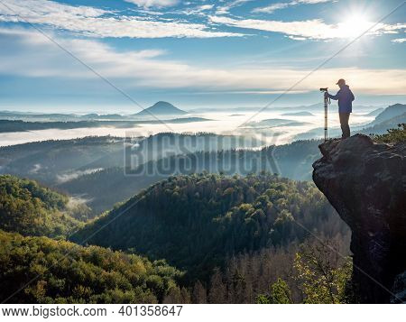 Photographer In Silhouette Carrying Tripod With Big Camera. Natural Photographer Hold Camera With Tr