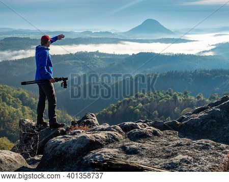 Photographer In Silhouette Carrying Camera  On Tripod. Natural Photographer Hold Camera With Tripod