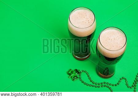 Two Glasses Of Dark Stout Beer And Traditional Clover Shaped Decor