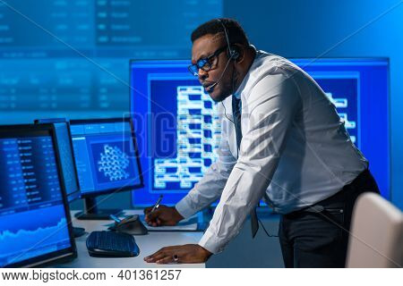 African-American broker works in office using workstation and analysis technology. Workplace of professional trader. Global financial markets, business, currency exchange and banking concepts.