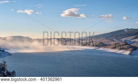 morning fog over mountain lake at foothills of Rocky Mountains - Horstooth Reservoir in northern Colorado, winter scenery with fresh snow
