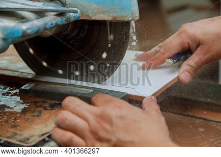 Worker A Man Sawing Ceramic Tiles At Tile Construction Works Tiling With A Circular Saw