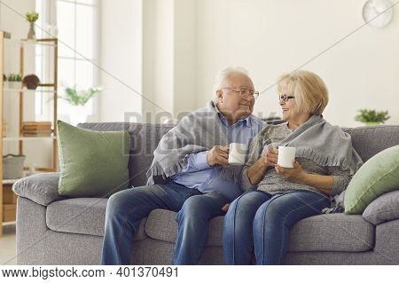 Smiling Mature Couple Grandparents Sitting Together On Sofa And Warming Up With Hot Tea