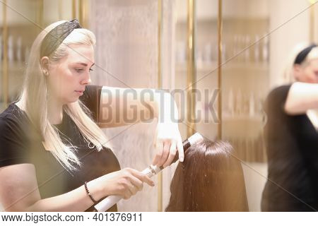 Portrait Of Hairdresser Doing Hairdo With Curling Iron. Haircutter Making Curls For Woman. Hair Styl