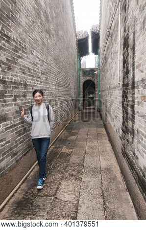 A Chinese Woman Leaning On A Brick Walling In A Narrow Alleyway In The Huangpu Village Scenic Area I