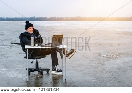 Elderly Businessman In Suit And Skates Holds Hockey Stick, Talking On Sell Phone, Works With Laptop