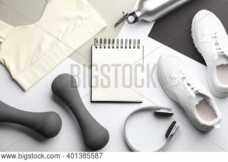 Flat Lay Composition With Sportswear, Notebook And Dumbbells On Color Background. Gym Workout Plan