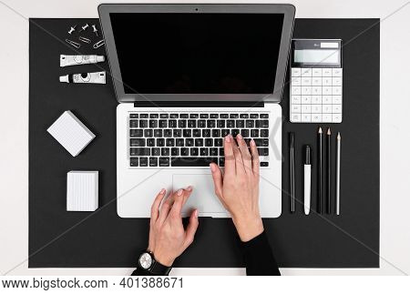 A Man Works With Laptop, Calculator, Pens, Pencils, Card, Phone On His Desktop Isolated On Balck Bac