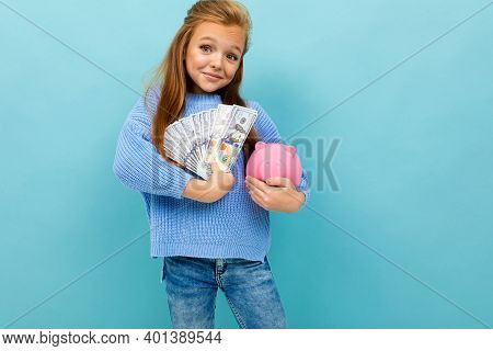 Beautiful European Girl Holding A Piggy Bank And Money In Hands On A Light Blue Wall.