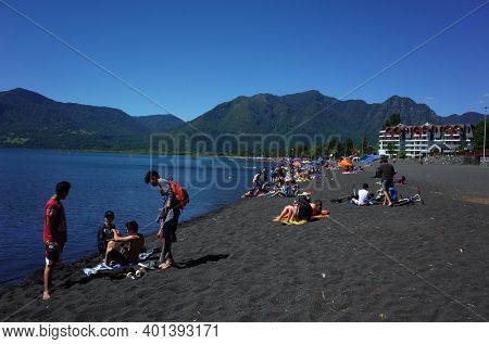 Pucon, Chile - December 1, 2018: Many people enjoy sun on black volcanic sandy beach of lake Villarrica, green mountains view, blue sky